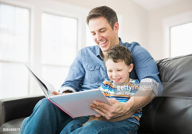Caucasian father and son reading on sofa