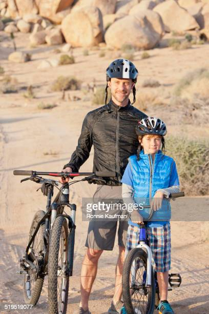 Caucasian father and son riding bicycles in desert landscape
