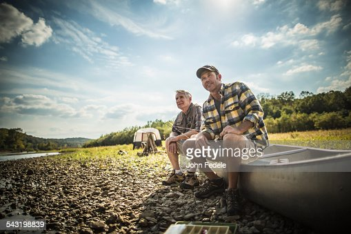 Caucasian father and son sitting in canoe on riverbed