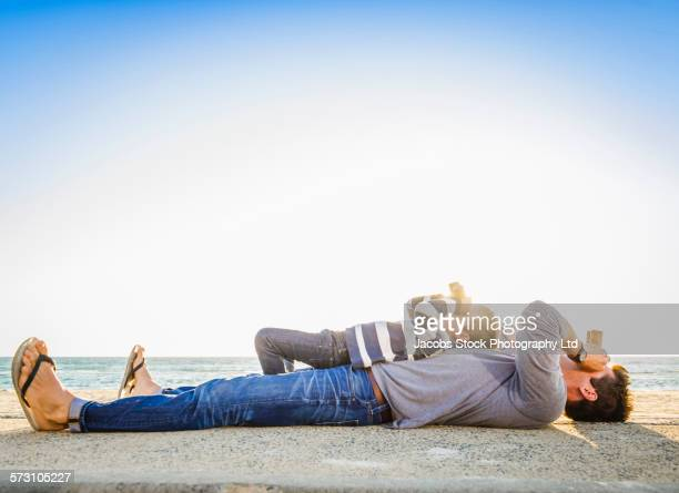 Caucasian father and son using binoculars on beach