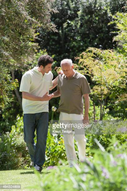 Caucasian father and son walking in park
