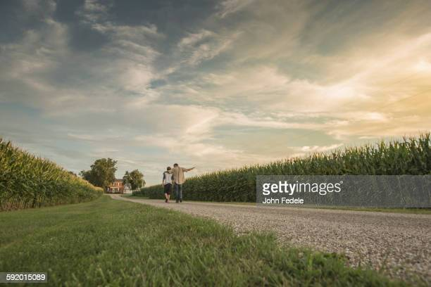 Caucasian father and son walking on dirt path by corn field
