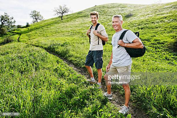 Caucasian father and son walking on dirt path
