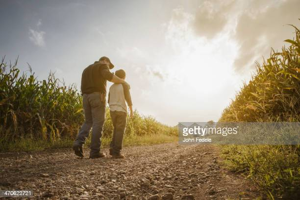 Caucasian father and son walking on dirt road through farm