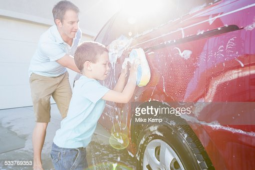 Caucasian father and son washing car in driveway
