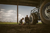 Caucasian father and son working on tractor