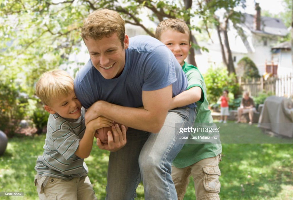 Caucasian father and sons playing football