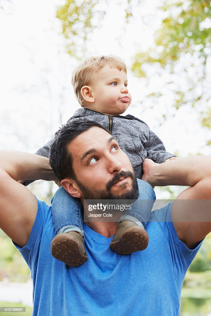 Caucasian father carrying baby son outdoors