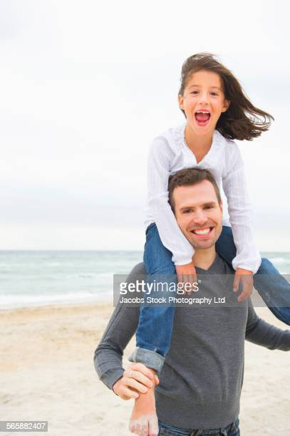 Caucasian father carrying daughter on shoulders on beach