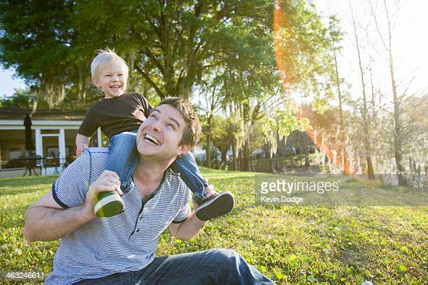 Caucasian father carrying son on shoulders in backyard