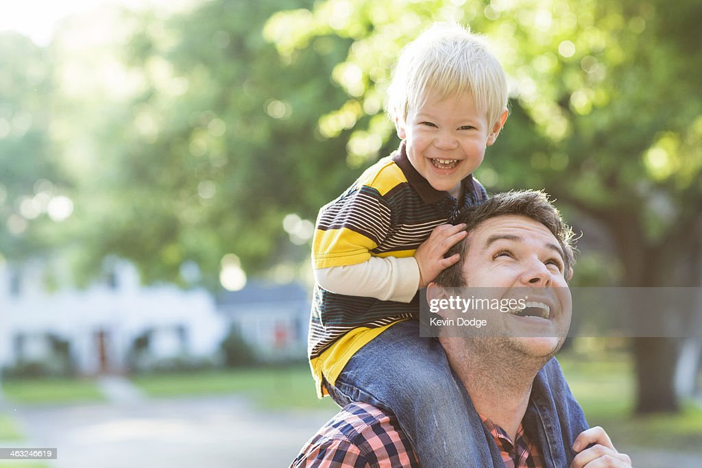 Caucasian father carrying son on shoulders