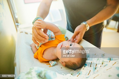 Caucasian father changing diaper of baby boy