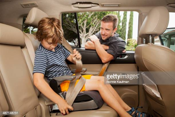Caucasian father fastening son into car seat