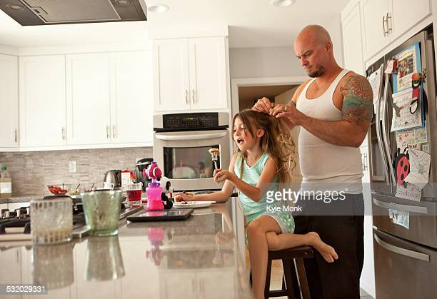 Caucasian father fixing hair of daughter in kitchen