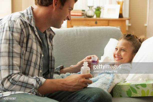 Caucasian father giving couch medicine to sick daughter