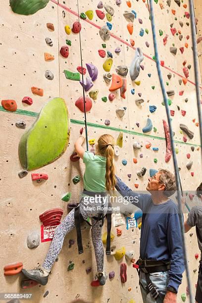 Caucasian father helping daughter climb rock wall indoors
