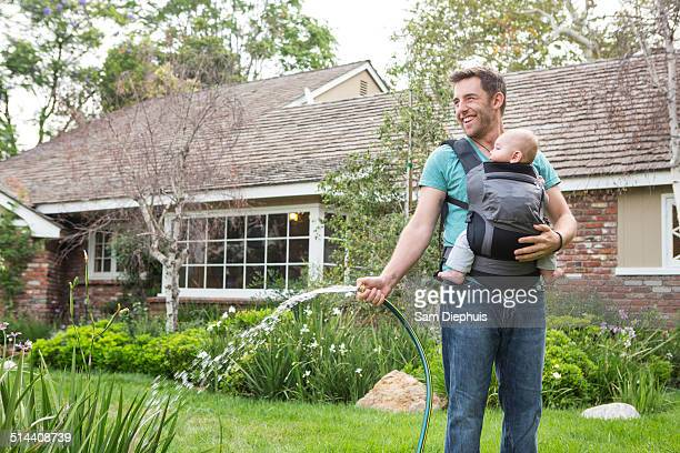 Caucasian father holding baby and watering plants