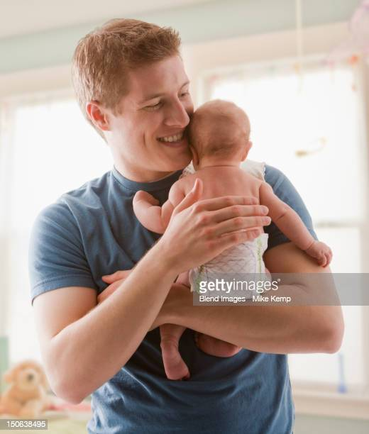 Caucasian father holding baby girl