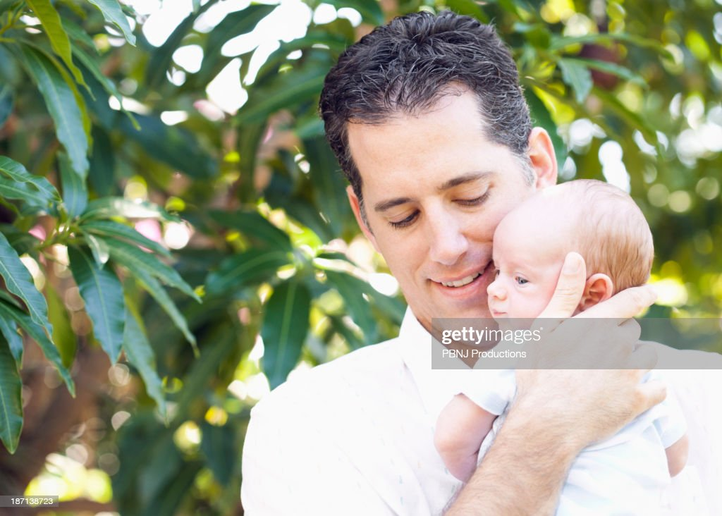 Caucasian father holding baby outdoors : Stock Photo