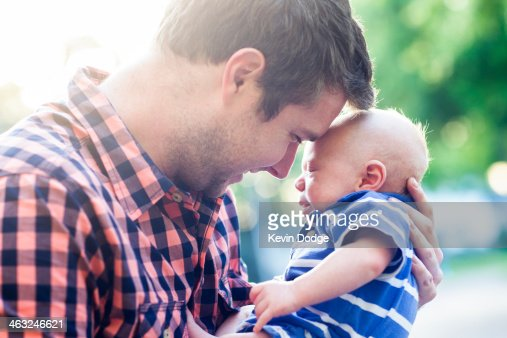 Caucasian father holding baby outdoors