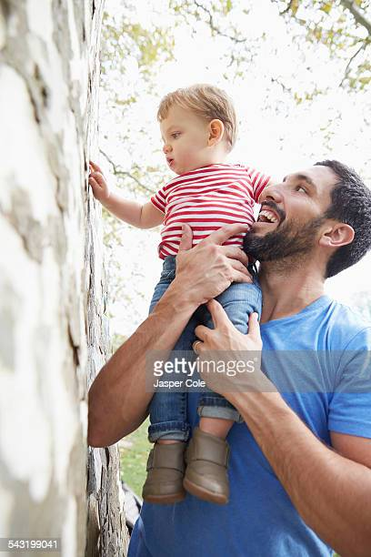 Caucasian father holding baby son under tree