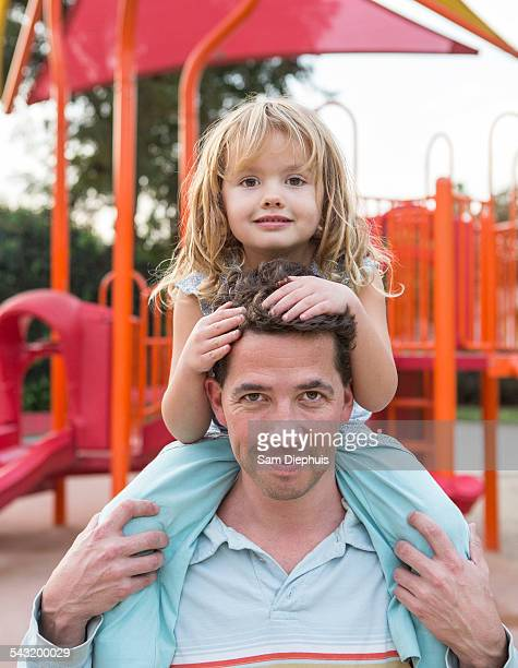 Caucasian father holding daughter at playground