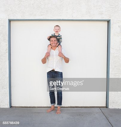 Caucasian father holding son on shoulders in driveway