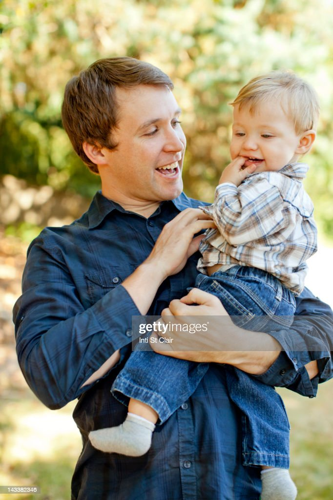 Caucasian father holding son outdoors : Stock Photo