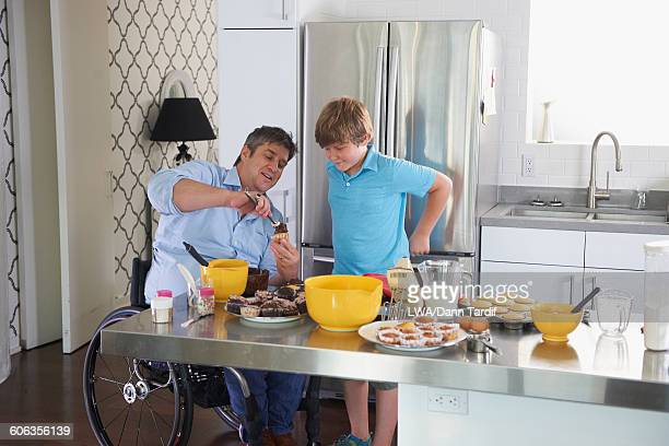 Caucasian father in wheelchair baking in kitchen with son