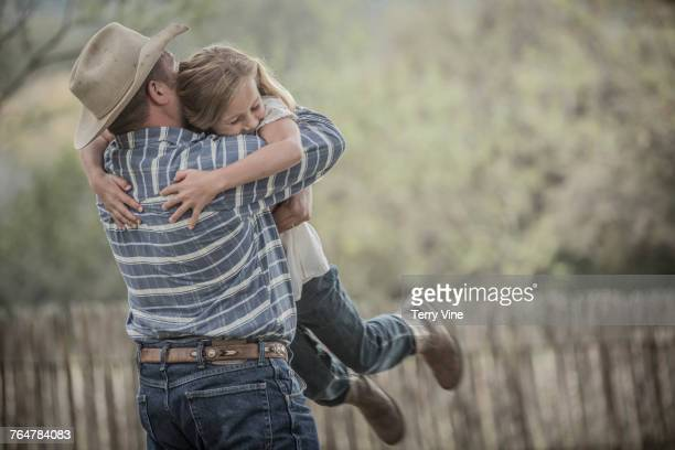 Caucasian father lifting and hugging daughter