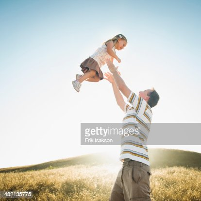 Caucasian father lifting daughter overhead in rural field