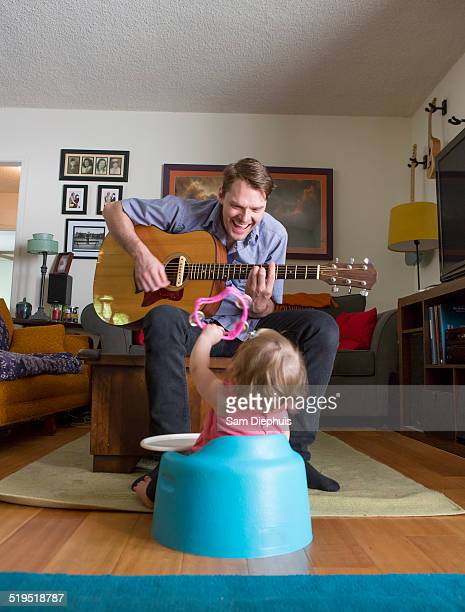 Caucasian father playing guitar for daughter
