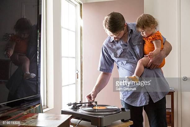 Caucasian father playing records with daughter