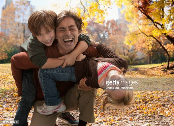 Caucasian father playing with son and daughter