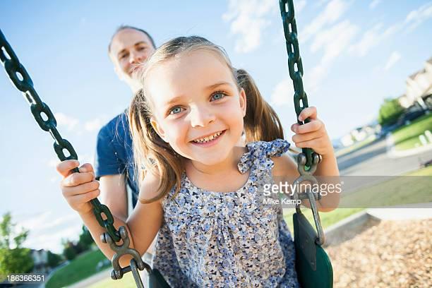 Caucasian father pushing daughter on swing