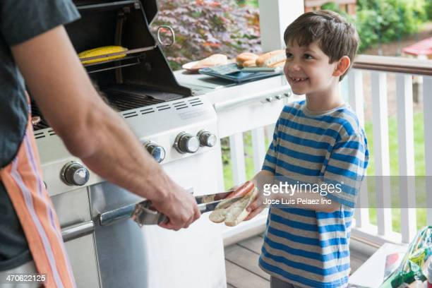 Caucasian father serving son hot dog