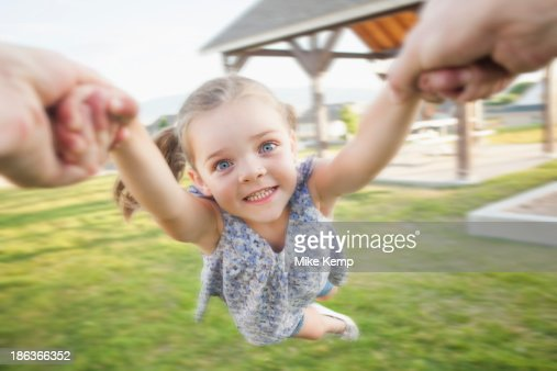 Caucasian father spinning daughter in park