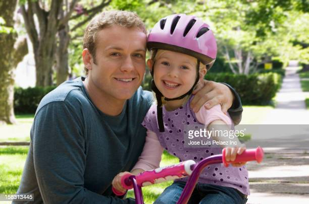 Caucasian father teaching daughter to ride bicycle