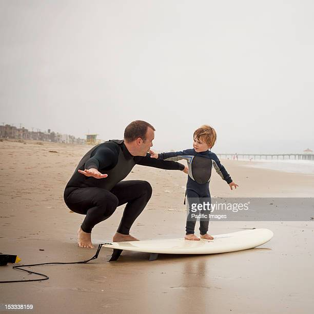 Caucasian father teaching son to surf
