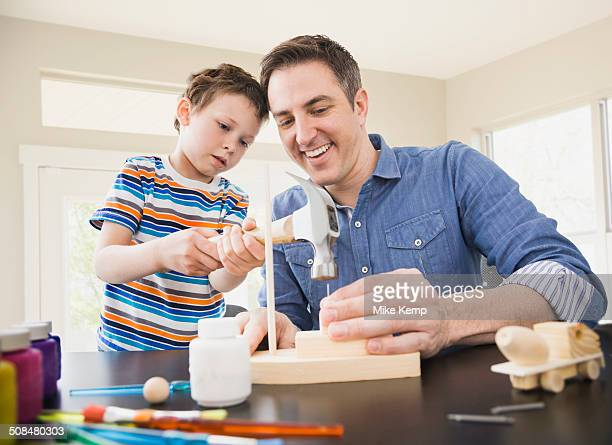 Caucasian father teaching son wood crafts