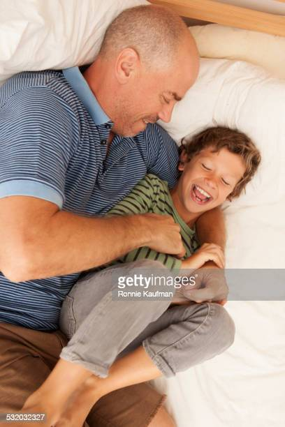 Caucasian father tickling son on bed