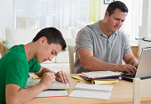 Caucasian father using laptop near studying son