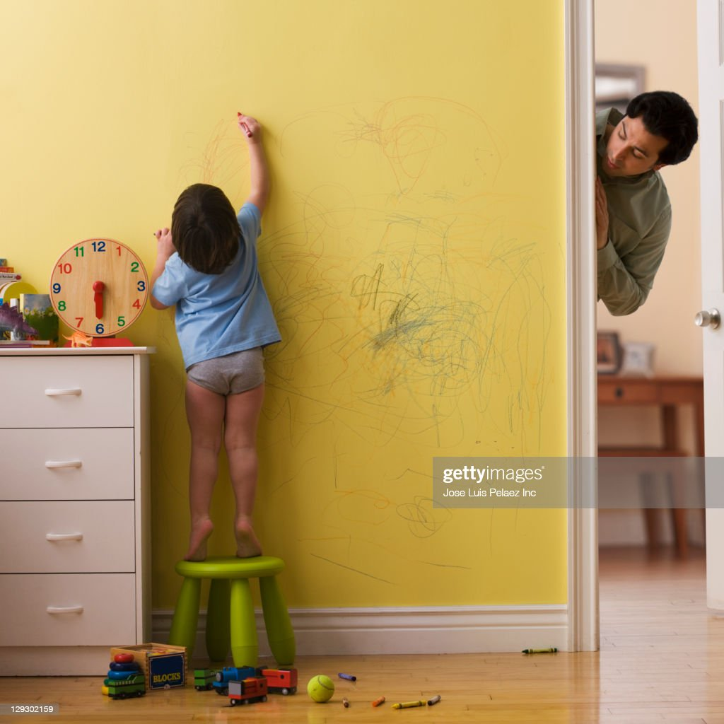 Caucasian father watching son drawing on wall with crayon
