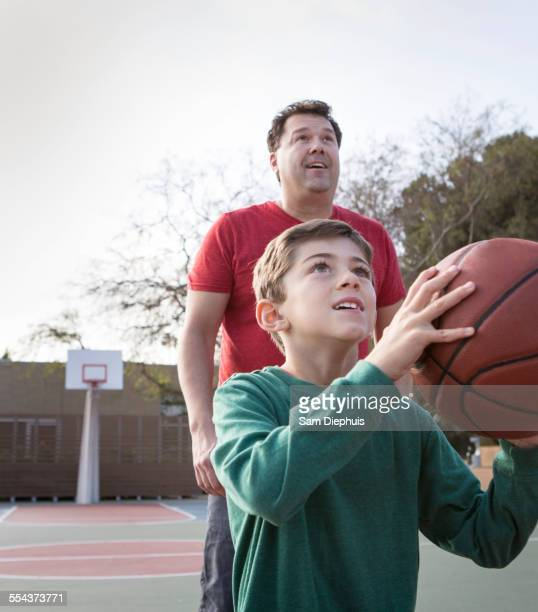 Caucasian father watching son hold basketball on court