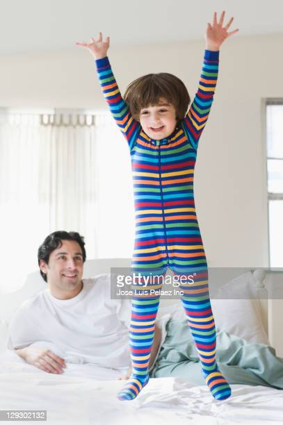 Caucasian father watching son jumping on bed