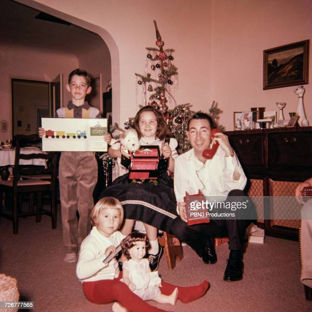 Caucasian father with son and daughters posing with Christmas gifts