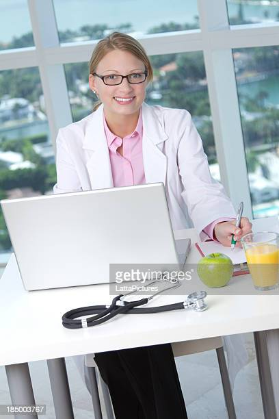Caucasian female doctor sitting behind desk with laptop
