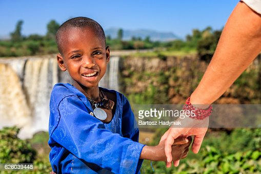 Caucasian female is holding young african child's hand