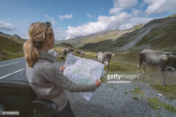 Caucasian female looks at road map near on mountain road, Switzerland