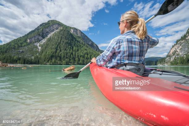 Caucasian female paddling canoe on mountain lake